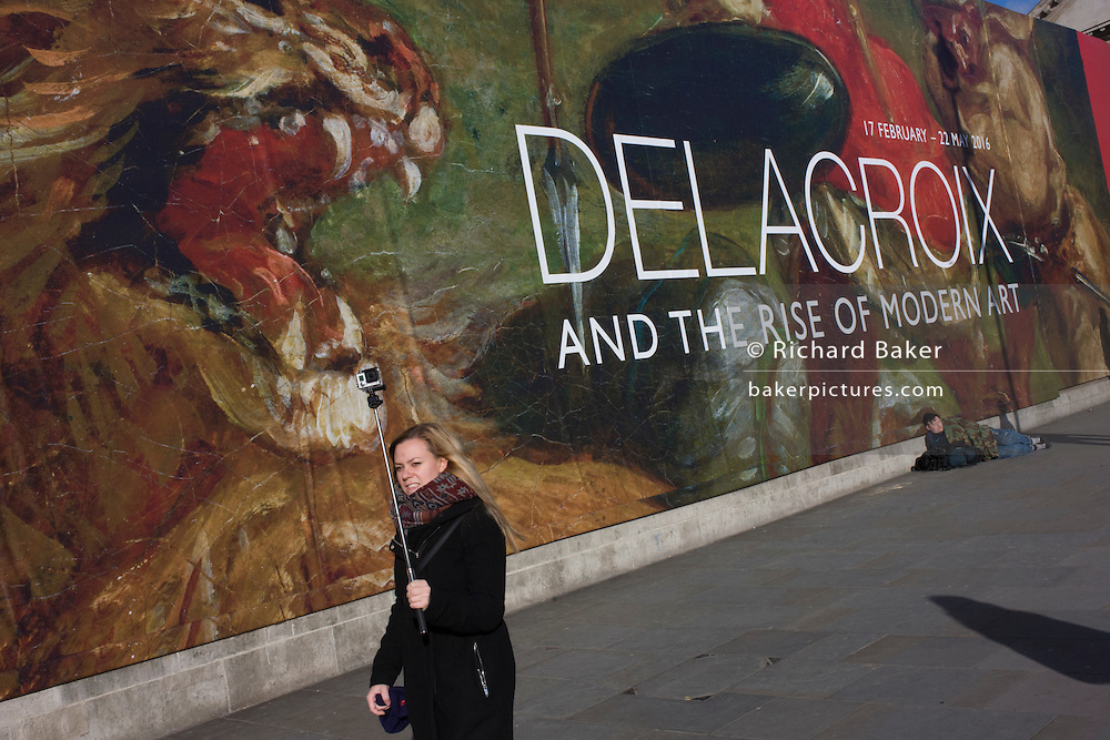 A woman and her selfie stick in front of the broad message on a hoarding announcing the next major exhibition by Delacroix at the National Gallery in London.