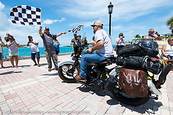 Rodney Sterling riding his 1945 Harley-Davidson WL Flathead over the finish line during the Cross Country Chase motorcycle endurance run from Sault Sainte Marie, MI to Key West, FL. (for vintage bikes from 1930-1948). The Grand Finish in Key West's Mallory Square after the 110 mile Stage-10 ride from Miami to Key West, FL and after covering 2,368 miles of the Cross Country Chase. Sunday, September 15, 2019. Photography ©2019 Michael Lichter.