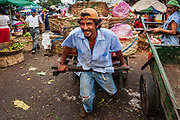 08 JANUARY 2007 - MANAGUA, NICARAGUA:  A man pulls a fruit delivery hand truck through Mercado Oriental, the main market that serves Managua, Nicaragua. The market encompasses dozens of square blocks and is the largest market in Central America.  Photo by Jack Kurtz