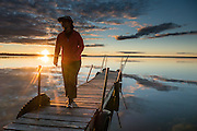 A person walks a dock in Lake Mitchell at sunset, at Lakeside Charlies restaurant, near Sun-N-Snow Motel, Cadillac, Michigan, USA.