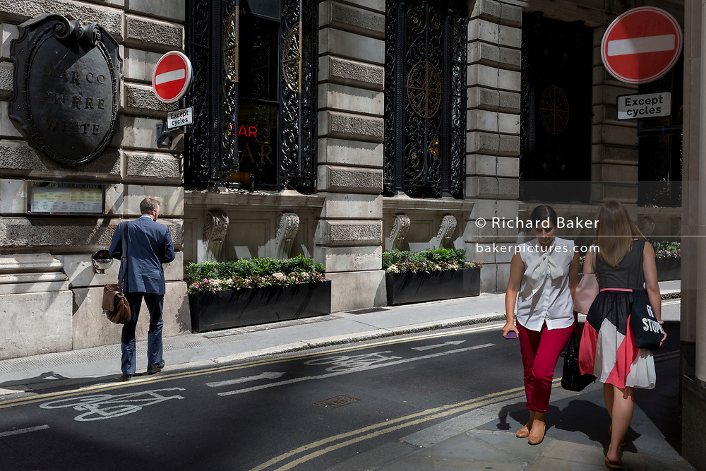 Two women walk along Finch Street, a narrow medieval-era lane in the City of London, the capital's historic financial district, on 2nd August 2018, in London, England.
