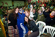 Male wrestler in blue gown posing with female foreign travellers. Lucha Libre wrestling origniated in Mexico, but is popular in other latin Amercian countries, including in La Paz / El Alto, Bolivia. Male and female fighters participate in the theatrical staged fights to an adoring crowd of locals and foreigners alike.