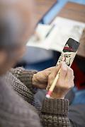 Close-up of senior man painting on figurine, Nozawaonsen, Japan