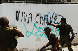 """Members f the national guard try and control a protest near the Cuban embassy.  The sign reads """"Long live Chavez"""".  Opposition to President Hugo Chavez  gathered at the embassy to protest the recent arrests in Cuba as well as what they view as the """"cubanization"""" of Venezuela.  Chavez supporters also came to express their views and the two groups clashed, throwing rocks and bottles."""