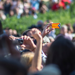 A Proces Constituent supporter takes a photo with a phone covered with a Catalan flag.
