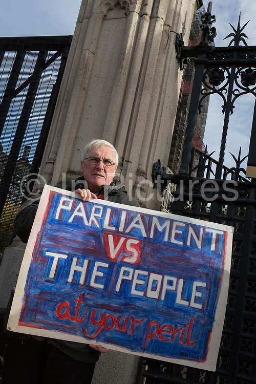 On the day that the EU in Brussels agreed in principle to extend Brexit until 31st January 2020 aka Flextension and not 31st October 2019, a Brexiters stands beneath the railings outside parliament with a placard warning of a confrontation between the People and Parliament, on 28th October 2019, in Westminster, London, England.