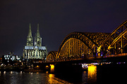Koln Cologne Dom Cathedral and the Hohenzollern Bridge, illuminated at night. Cologne, Germany.