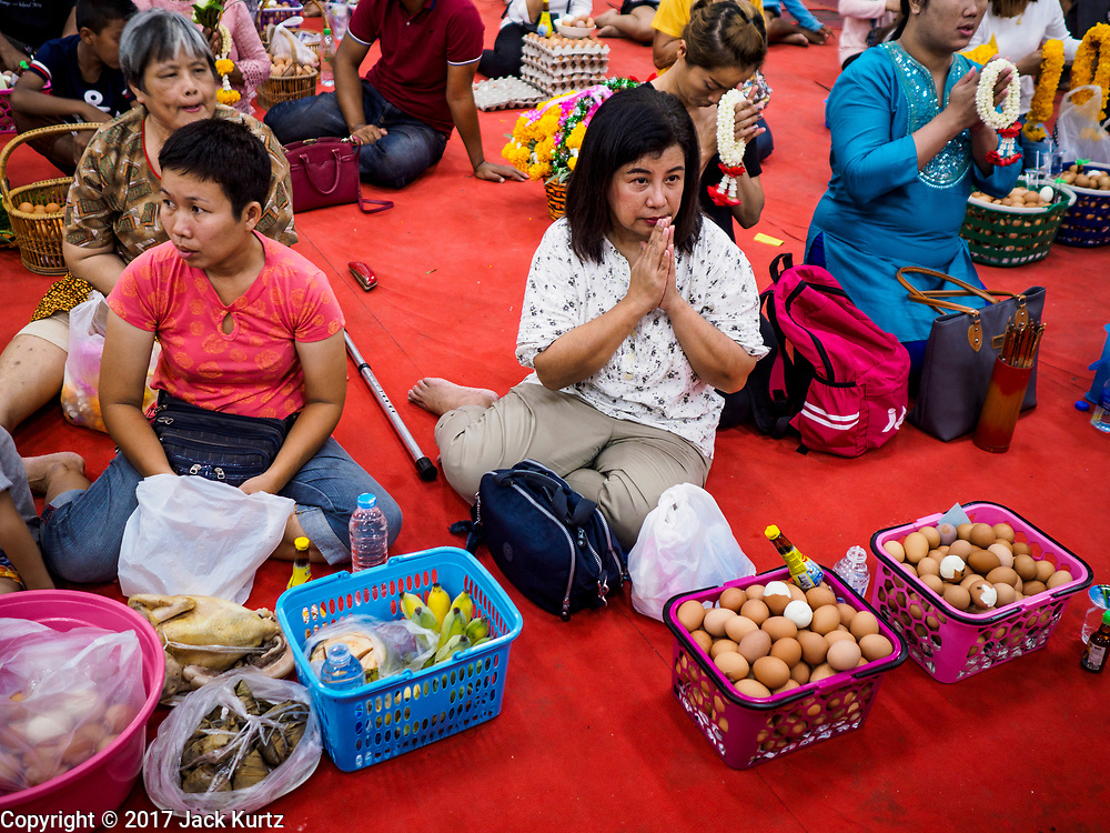 31 MAY 2017 - CHACHOENGSAO, THAILAND:  A woman with an offering of hard boiled eggs prays at Wat Sothon (also spelled Sothorn) in Chachoengsao, Thailand. The temple is one of the largest and most visited in Thailand. People make merit by paying to wrap the Buddha statues in orange robes. The temple is most famous because people leave hard boiled eggs as an offering at the temple. They ask for business success or children and leave hundreds of hard boiled eggs.      PHOTO BY JACK KURTZ