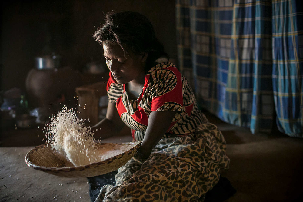 Margaret sifts through the rice in her hut in Gulu. She was abducted at the age of 11 in Acholi-bur village and was assigned to a commander two years later who had 13 wives. She also started a military training at that time and spent eight years as a soldier. She gave birth to two daughters in the bush. When she was 19 years old, a mortar attack at the frontline hit her arm and the chest, resulting in the amputation of one arm.