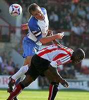 Photo: Frances Leader.<br />Brentford v Swindon Town. Coca Cola League 1.<br />15/10/2005.<br /><br />Brentford Lloyd Owusu and Swindons Sean O'Hanlon head the ball.