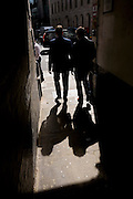 Two businessmen walk through a central London alleyway with their strong shadows on the pavement.