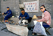 Chinese cobbler making and repairing shoes in backstreets of Peking, now Beijing, China in the 1980s
