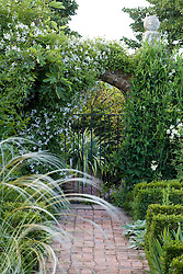 Arch covered with Clematis 'Alba Luxurians' in the White Garden at Sissinghurst Castle. Stipa barbata in the foreground