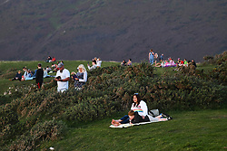 © Licensed to London News Pictures. 21/09/2020. City, UK. People pack the cliffs of Rhossili Bay on Swansea's Gower coast, to watch a spectacular sunset behind Worm's Head at the end of a glorious day in south Wales, bringing Summer to an end. The location is one of the best to watch a sunset in the UK and is ever popular with tourists and locals. <br /> . Photo credit: Robert Melen/LNP