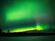 View of the Aurora Borealis from a frozen lake in Lemmenjoki National Park, Lapland, Finland.