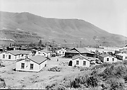 9305-B7053. Bird's-eye view of the 'new' housing provided by the Army engineers surrounding the longhouse after occupancy in summer 1950. Chief Tommy Thompson's house is on the extreme left.