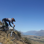 Tyler Brooker from Christchurch in action during the New Zealand South Island Downhill Cup Mountain Bike series held on The Remarkables face with a stunning backdrop of the Wakatipu Basin. 150 riders took part in the two day event. Queenstown, Otago, New Zealand. 9th January 2012. Photo Tim Clayton
