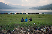 Three seated young men look out over Lake Phewa Tal and passing boats in Pokhara, Nepal.