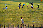 As a woman runner passes-by, young male footballers train in Ruskin Park a south London green space, during late afternoon, on 21st September 2021, in London, England.
