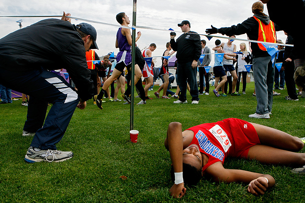 Eisenhower's Timothy Cummings lays on the ground Saturday after collapsing at the finish in the boys 4A race, placing 18th with a time of 15:56. Eisenhower won the team competition, the first time a non-Spokane team has won the Big School Boys Championship since 1987, the last time Eisenhower clinched the title.