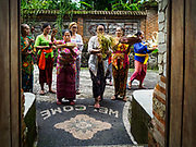 """08 AUGUST 2017 - UBUD, BALI, INDONESIA: Women pray at the entrance of their family compound during a ceremony to honor a family temple in Ubud, Bali. Balinese Hindus have a 210 day calender and every almost every family compound on Bali has a family temple. Once a year (or every 210 days) families celebrate the """"birthday"""" of their temple with a ceremony.     PHOTO BY JACK KURTZ"""