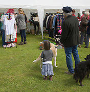 People browsing vintage clothes stall at village fete, Bawdsey, Suffolk, England