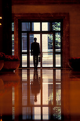 Stock photo of a silhouette of a man inside of a building exiting through the front door