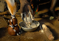 """Ahmad Msham, 39, a bush doctor from Chidodo settlement in Lindi, Tanzania prepares a mix using maize flour and tree roots next to a kibuyu vessel that holds lion's hair that he uses for """"white magic"""" when spirit lions are thought to be eating villagers. (Photo by Ami Vitale)"""