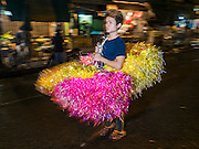 """21 DECEMBER 2015 - BANGKOK, THAILAND: A plastic flower vendor on the street in front of Pak Khlong Talat, also called the Flower Market. The market has been a Bangkok landmark for more than 50 years and is the largest wholesale flower market in Bangkok. A recent renovation resulted in many stalls being closed to make room for chain restaurants to attract tourists. Now Bangkok city officials are threatening to evict sidewalk vendors who line the outside of the market. Evicting the sidewalk vendors is a part of a citywide effort to """"clean up"""" Bangkok.       PHOTO BY JACK KURTZ"""