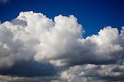 Heavy cumulus clouds low in blue sky, UK
