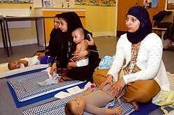 Baby massage class at NHS clinic run by Community Health Worker; Bradford; Yorkshire UK