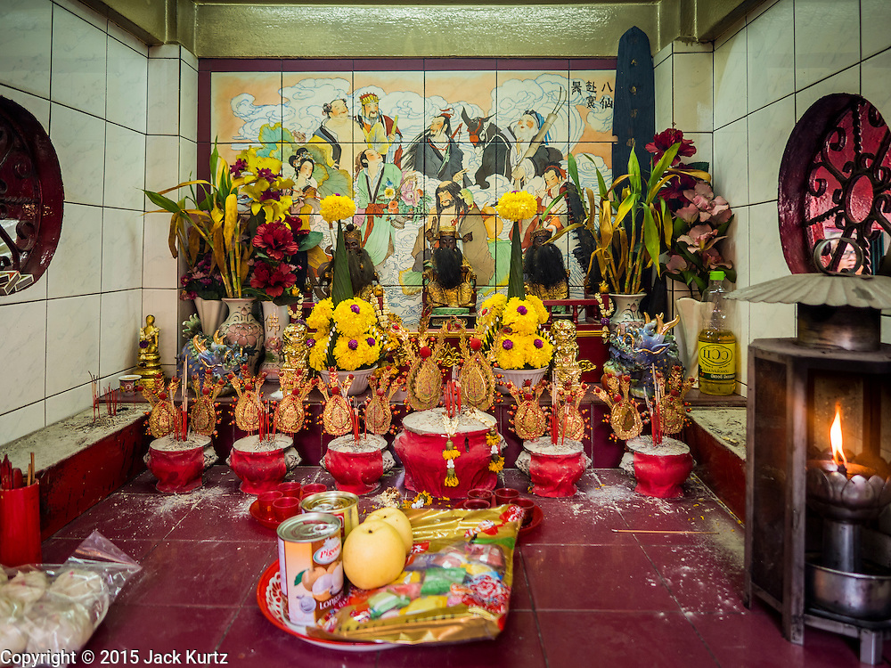 28 AUGUST 2015 - BANGKOK, THAILAND:  The alter of a small shrine in Bangkok's Chinatown on Hungry Ghost Day. Mahayana  Buddhists believe that the gates of hell are opened on the full moon of the seventh lunar month of the Chinese calendar, and the spirits of hungry ghosts allowed to roam the earth. These ghosts need food and merit to find their way back to their own. People help by offering food, paper money, candles and flowers, making merit of their own in the process. Hungry Ghost Day is observed in communities with a large ethnic Chinese population, like Bangkok's Chinatown.     PHOTO BY JACK KURTZ