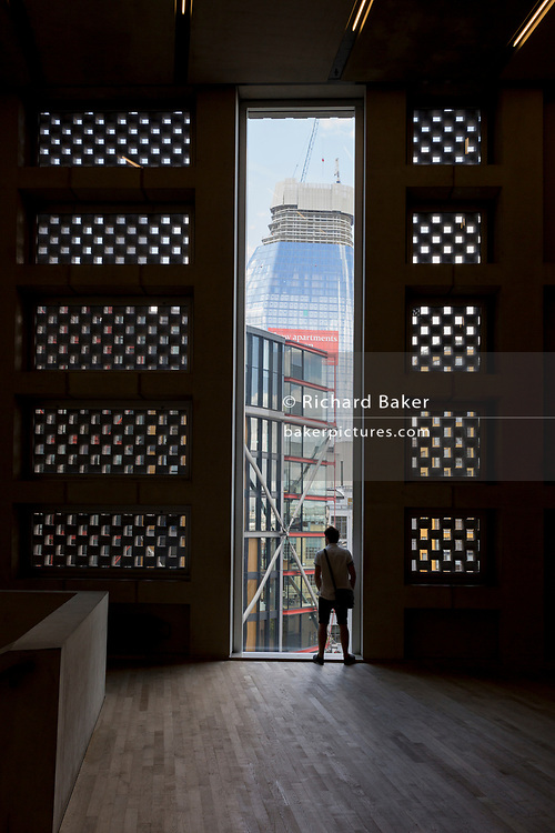 A visitor to Tate Modern looks out of a tall window towards the apartments opposite, whose owners object to intrusion, on the Southbank, on 14th May 2017, in London, England.