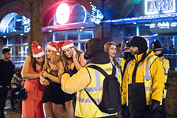 """© Licensed to London News Pictures . 16/12/2017. Manchester, UK. Three women dressed as Santa Claus huddle together for warmth as they wait for a taxi at Deansgate Locks . Revellers out in Manchester City Centre overnight during """" Mad Friday """" , named for historically being one of the busiest nights of the year for the emergency services in the UK . Photo credit: Joel Goodman/LNP"""