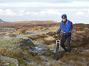 A portrait of cyclist cycling on a bridleway over the North York Moors on a frosty Winter's morning, North Yorkshire, UK