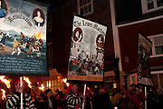 Lewes, Sussex. Bonfire Night November 5th 2013. Members of Cliffe Bonfire Society parade with banners explaining the history of the night.