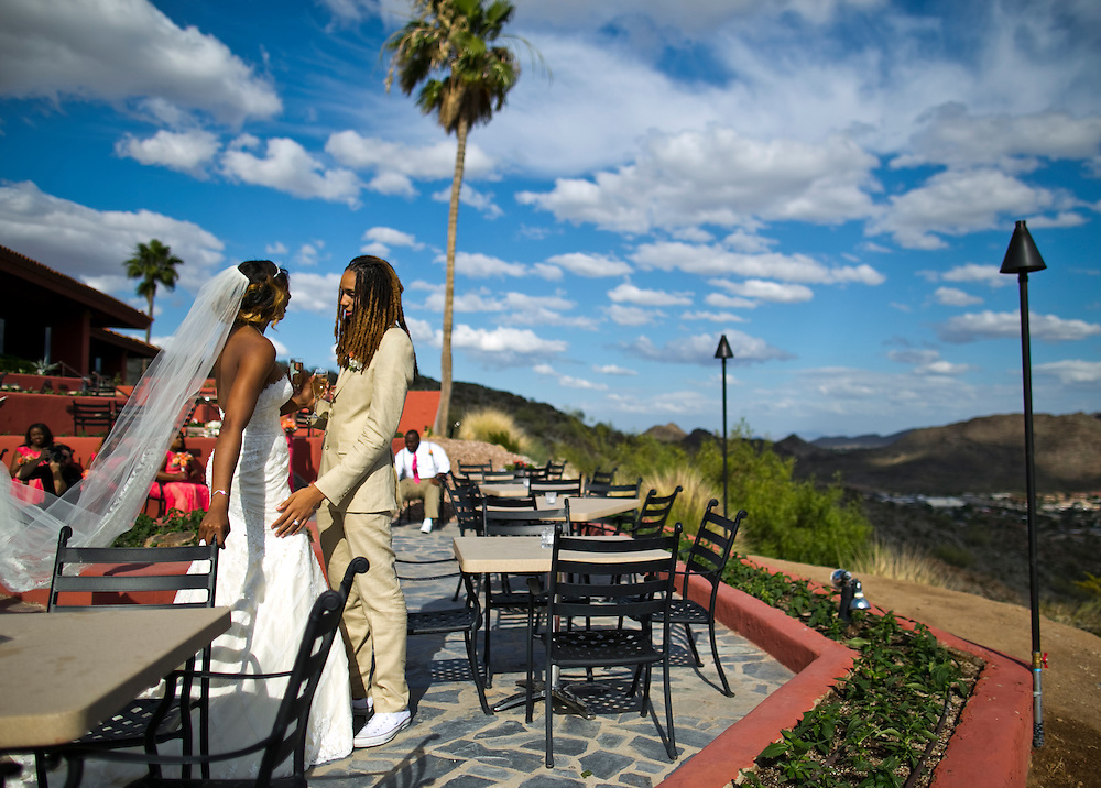 WNBA stars Glory Johnson, left and Brittney Griner wait to take photographs with the wedding party during their wedding ceremony at the Pointe Hilton Tapatio Cliffs Resort in Phoenix, Ariz. on May 8, 2015.
