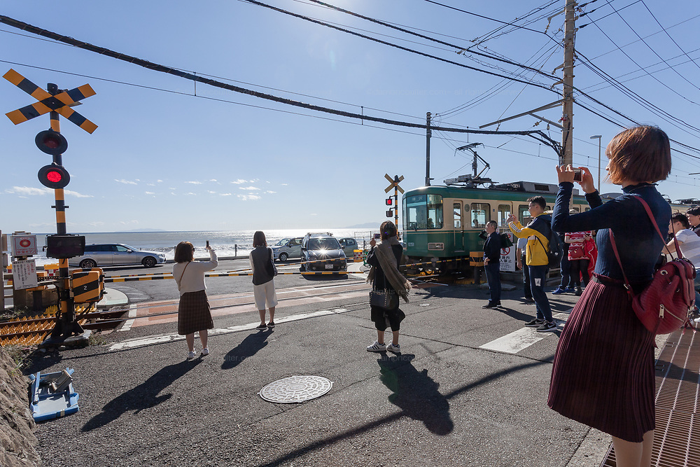 Chinese and Korean tourist take pictures and pose at Kamakura Kokomae crossing on the Enoden Lne near near Kamakura, Kanagawa, Japan. Monday October 23rd 2017. The crossing features in the popular animation of the Slam Dunk manga (comic Books)