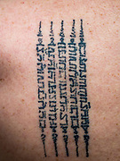 "27 MAY 2015 - BANGKOK, THAILAND: A Sak Yant tattoo prayer tattooed into a man's back in Ajarn Neng Onnut's home in Bangkok. Sak Yant (Thai for ""tattoos of mystical drawings"" sak=tattoo, yantra=mystical drawing) tattoos are popular throughout Thailand, Cambodia, Laos and Myanmar. The tattoos are believed to impart magical powers to the people who have them. People get the tattoos to address specific needs. For example, a business person would get a tattoo to make his business successful, and a soldier would get a tattoo to help him in battle. The tattoos are blessed by monks or people who have magical powers. Ajarn Neng, a revered tattoo master in Bangkok, uses stainless steel needles to tattoo, other tattoo masters use bamboo needles. The tattoos are growing in popularity with tourists, but Thai religious leaders try to discourage tattoo masters from giving tourists tattoos for ornamental reasons.     PHOTO BY JACK KURTZ"