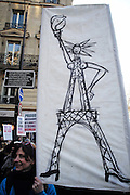 January, 21st, 2017 - Paris, Ile-de-France, France: Woman as Eiffel Tower Protest banner. Thousands of protesters in Paris join anti-Trump Women's March around the world.