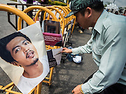 07 JULY 2015 - BANGKOK, THAILAND: A man looks at the pictures of students arrested by the Thai junta during a rally in support of the students. The pictures were hung on a barricade in front of the Ministry of Defense. About 100 people gathered in front of the Ministry of Defense in Bangkok Tuesday to support 14 university students arrested two weeks ago for violating orders against political assembly. They're facing criminal trial in military courts. The courts ordered their release Tuesday because they can only be held for two weeks without trial, the two weeks expired Tuesday and the military court chose not to renew their pretrial detention. The court order was not an acquittal. They still face trial and possible prison sentences if convicted.        PHOTO BY JACK KURTZ