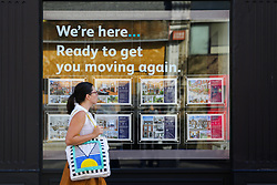 © Licensed to London News Pictures. 02/09/2020. London, UK. A woman walks past a display of properties for sale in an estate agent's window. According to new figures released by Nationwide, UK houses prices were at an all-time high in August 2020 after their biggest monthly rise since 2004, as buyers took advantage of a stamp-duty holiday. The average sale price of a home jumped £3,188 to £224,123 in August. Photo credit: Dinendra Haria/LNP