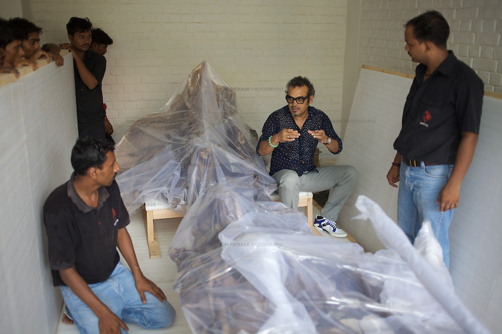 """Subodh Gupta, contemporary artist in his studio in Gurgaon with freight staff about to collect a sculpture for delivery to a European exhibition.  ..Gupta's most celebrated sculptures are constructed from common domestic items including the steel pots and pans that are a feature every Indian home. Of the kitchen-ware that forms the basis of his work, Gupta says,..""""The poor, the middle class and the rich use it at home. In this country, how many people have the utensils but they starve because there is no food?""""..Gupta was brought up, one of six children, to a railway-worker father in a north Indian village. ..Gupta's work fetches such huge sums of money. Two versions of his Mind Shut Down, modeled on the human skull and constructed entirely of steel kitchen utensils recently sold for EUR1 million each...Photo: Tom Pietrasik.Gurgaon, Haryana. India. .July 23rd 2009"""