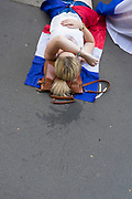 A woman rests on the floor while the match between France and Croatia in the World Cup Final is transmitted in a café. Paris, France