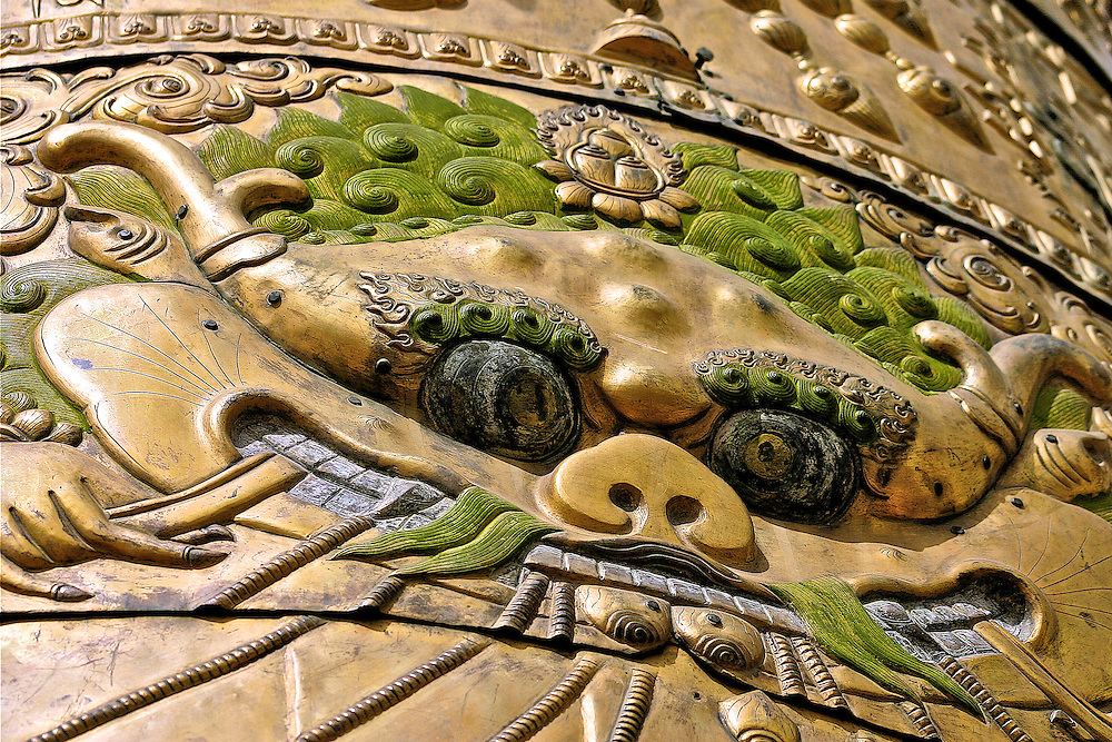 This is one of many faces artfully sculpted into brass towers that ornately decorate the roof of a tibetan monastery in downtown lhasa tibet
