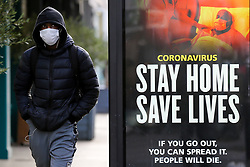 "© Licensed to London News Pictures. 09/01/2021. London, UK. A man wearing a protective face covering walks past the Government's ''Stay Home, Save Lives' Covid-19 publicity campaign poster in north London, as the number of cases of the mutated variant of the SARS-Cov-2 virus continues to spread around the country. The message in the advertising campaign poster asks people to act like they have Covid and Prime Minister Boris Johnson has said that the public should ""stay at home"". Photo credit: Dinendra Haria/LNP"