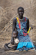 Adol Awar works on her beadwork with one of her three children, Ajier Dau, 1 1/2 next to her in their makeshift home in the forests of Yolakot, South Sudan in Lake State. An estimated 716,100 have been displaced in South Sudan with an additional 166,900 fleeing to neighboring countries as a result of conflict that erupted in mid-December 2013. The Nile has become a lifeline for the people who have sought shelter along its shores. Catholic Relief Services and Caritas Internationalis have been responding with latrines, hand washing stations, and emergency shelter kits and non food items such as kitchen materials and hygiene materials.
