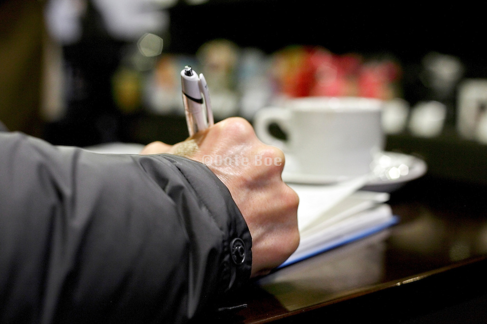 hand of person writing with coffee cup