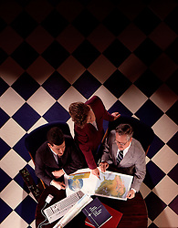 Overhead view office executive workers review geographic maps