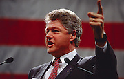 President Bill Clinton speaks in front of a large American flag.